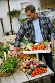 A man holding a crate of fresh vegetables