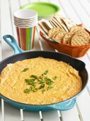 Mexican Cheese Dip in a Skillet with a Basket of Crackers