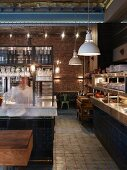 English restaurant in historic hall with brick wall, counter with decorative blue tiles and retro-style pendant lamps