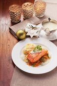 Salmon with a herbal foam sauce and carrot strips