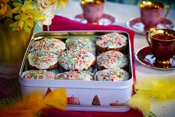 Fairy cakes topped with icing and hundreds-and-thousands