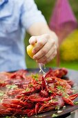 Squeezing lemon juice onto barbecue crayfish
