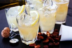 Apple and grapefruit drink with ice and grapefruit slices and spiced nuts