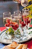 Sparkling wine with raspberries in several glasses on buffet table