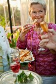 Blonde Frau isst Käsegebäck auf einer Party