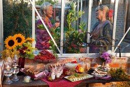 Partybuffet für das Krebsfest im Garten, im Hintergrund zwei ältere Damen