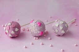 Three purple cake pops with sugar hearts