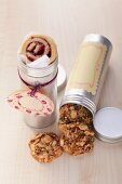 Cookies with mixed nuts and marmalade snails in aluminum tins