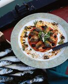 Baked mackerel on a bed of tomatoes, olives and herbs