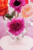 Flowers in glass vases and heart-shaped card reading 'Be my valentine'