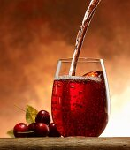 Pouring cherry juice into a glass