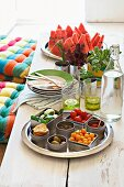 Mediterranean nibbles in dishes alongside glasses and plates on a rustic vintage table made from white wooden planks
