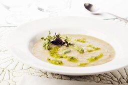 Bowl of Creamy Artichoke Soup with Pesto and Fresh Purple Basil and Lemon Basil