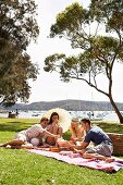 Young people picnicking on the grass by the lake