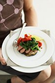 Woman serving plate of lamb fillet and vegetables