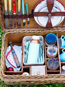 A picnic basket filled with crockery, glasses and cutlery