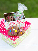 Cookies decorated with colourful chocolate beans in a biscuit tin
