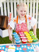 A girl selling cupcakes at a school fete