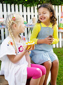 Two girls eating sweets at a school fete