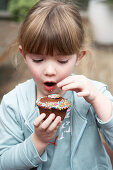 A little girl eating a chocolate cupcake