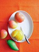 Fresh mangos, one peeled
