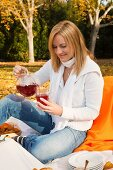 Woman pouring fruit tea at autumn picnic