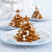 Biscuits stacked into Christmas trees decorated with icing sugar