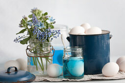 An arrangement of grape hyacinths, dye and eggs