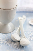 Sea salt on porcelain spoons next to an egg cup