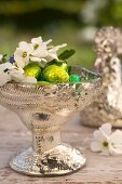 A silver bowl of chocolate eggs, forget-me-not, garden jasmine and sloe berries