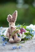 A toy rabbit with a snake's head flower in front of a wreath of forget-me-not
