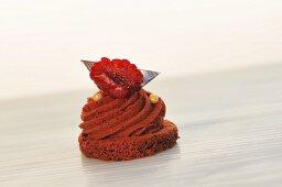 A mini chocolate cake topped with a raspberry
