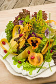 A colourful summer salad with pansies and courgette flowers