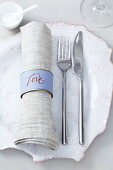 A place setting with cutlery and a homemade napkin ring made from a small tin can