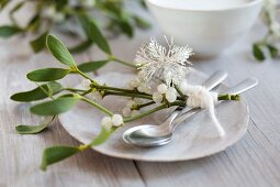 A Christmas place setting with mistletoe and a snowflake