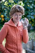 A woman drinking a glass of water in a garden