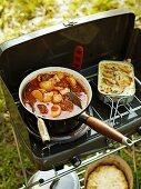 Fischeintopf mit Chorizo und Kartoffelgratin auf einem Campingkocher