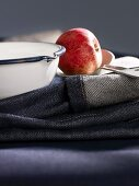 A red apple on top of jeans