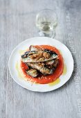 Sardines on a bed of aubergines with a pepper sauce