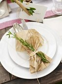 Cutlery wrapped in baking paper decorated with a sprig of rosemary and a place card