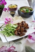 Crispy fried duck with raw vegetables and pancakes