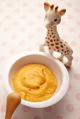 Carrot puree in a little dish next to a toy giraffe