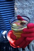 Person holding a glass of apple punch