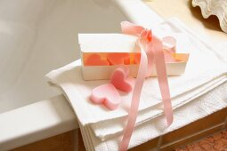 A heart-shaped bar of soap in a gift box tied with a silk ribbon