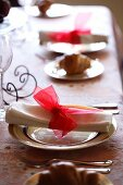 A Christmas place setting with a rolled napkin and a red chiffon bow