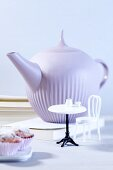 A teapot with doll's furniture and muffins