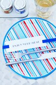 Cutlery and a card on a ribbon on a striped plate