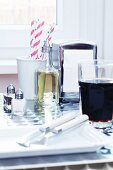 A bottle of vinegar, a napkin dispenser, straws, salt and pepper shakers, a place setting and a glass of cola on a table