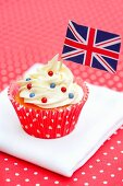 A cupcake decorated with a small flag and sugar beads