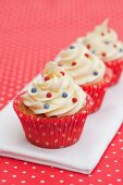 Three cupcakes decorated with red and blue sugar beads